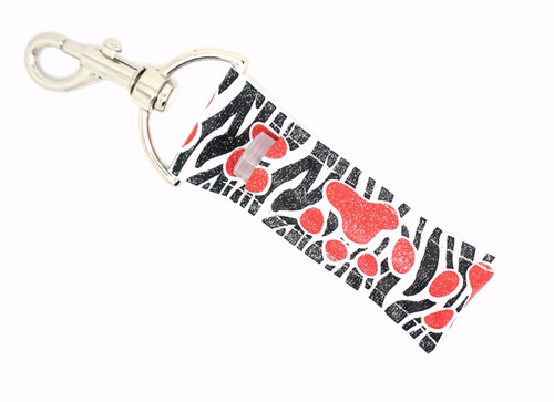Lip Balm Holder Black and White Zebra with Red Glitter Paw Prints  Each Lip Balm / Chapstick Holder is HANDMADE with a high-quality material! Our unique design's and clasp offer both style and functionality. The hook is also on a swivel head so the lip balm always falls back down and never gets stuck upside down, this is where most lip balm holders lose your lip balm or chapstick! The holder is designed to snuggly fit nice and cozy any standard chapstick or lip balm. This ensures that the lip balm / chapstick won't fall out when needed most.   BENEFITS: Misplacing or Losing your chapstick is the worst!! Don't let that happen again and buy the perfect solution! Our Lip Balm / Chapstick Holder Keychain will make sure you always have your Gettin Lippy lip balm at hand when desperately needed. Our cute fun designs will compliment anything. Attach it to your keys, lanyard, back-pack, bag, purse, or anywhere your little heart desires with our easy open clasp!   PERFECT GIFTS: A simple gift can go a long way. Everyone needs something cute and functional. Buy now for stocking stuffers, birthday party, a team gift or for a daughter, friend, wife, girlfriend, colleague, student, teacher, etc!   BUY WITH CONFIDENCE: Read the reviews! Our Gettin Lippy Lip balm holders are the number one rated lip balm holders on the market! If you don't LOVE our product, we offer 100% Money Back GUARANTEE no questions asked.   PACKAGE INCLUDES:  1 Unique Lip Balm / Chapstick holder. Each Holder is 6.5 inches (with hook) x 1.5 inches. **NOTE: Gettin Lippy lip balms in pictures are not included but click on the link below and get the best multi-flavored lip balm on the market:   https://gettinlippy.com/gettin-lippyoriginal-line/     MADE IN THE USA!!