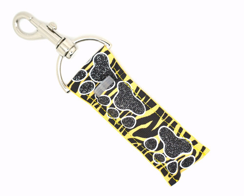Black and glitter Paw prints on top of Black and Yellow Zebra print Lip Balm Holder   This lip balms holder is very durable with a stainless steel hook that is easily attached and unattached to a purse, keys, backpack, or lanyard. This lip balm holder has a Black with glitter paw prints on top of black and yellow zebra print!  MADE IN THE USA!!