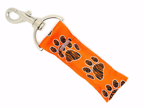 Orange with Black Zebra Paw Prints Lip Balm Holder   Each Lip Balm / Chapstick Holder is HANDMADE with a high-quality material! Our unique design's and clasp offer both style and functionality. The hook is also on a swivel head so the lip balm always falls back down and never gets stuck upside down, this is where most lip balm holders loose your lip balm or chapstick! The holder is designed to snuggly fit nice and cozy any standard chapstick or lip balm. This ensures that the lip balm / chapstick won't fall out when needed most.    BENEFITS: Misplacing or Losing your chapstick is the worst!! Don't let that happen again and buy the perfect solution! Our Lip Balm / Chapstick Holder Keychain will make sure you always have your Gettin Lippy lip balm at hand when desperately needed. Our cute fun designs will compliment anything. Attach it to your keys, lanyard, back-pack, bag, purse, or anywhere your little heart desires with our easy open clasp!   PERFECT GIFTS: A simple gift can go a long way. Everyone needs something cute and functional. Buy now for stocking stuffers, birthday party, a team gift or for a daughter, friend, wife, girlfriend, colleague, student, teacher, etc! Also make sure you checkout our custom lip balms!   BUY WITH CONFIDENCE: Read the reviews! Our Gettin Lippy Lip balm holder's are the number one rated lip balm holder on the market! If you don't LOVE our product we offer 100% Money Back GUARANTEE no questions asked.   PACKAGE INCLUDES:  1 Unique Lip Balm / Chapstick holder. Each Holder is 6.5 inches (with hook) x 1.5 inches. **NOTE: Gettin Lippy lip balms in pictures are not included but click on the link below and get the best multi-flavored lip balm on the market:   https://gettinlippy.com/gettin-lippyoriginal-line/     MADE IN THE USA!!
