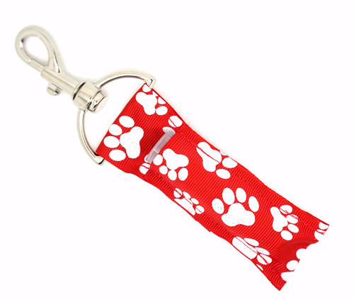 Red with White Glitter Print Paw Prints Lip Balm Holder    Each Lip Balm / Chapstick Holder is HANDMADE with a high-quality material! Our unique design's and clasp offer both style and functionality. The hook is also on a swivel head so the lip balm always falls back down and never gets stuck upside down, this is where most lip balm holders loose your lip balm or chapstick! The holder is designed to snuggly fit nice and cozy any standard chapstick or lip balm. This ensures that the lip balm / chapstick won't fall out when needed most.  BENEFITS: Misplacing or Losing your chapstick is the worst!! Don't let that happen again and buy the perfect solution! Our Lip Balm / Chapstick Holder Keychain will make sure you always have your Gettin Lippy lip balm at hand when desperately needed. Our cute fun designs will compliment anything. Attach it to your keys, lanyard, back-pack, bag, purse, or anywhere your little heart desires with our easy open clasp!    PERFECT GIFTS: A simple gift can go a long way. Everyone needs something cute and functional. Buy now for stocking stuffers, birthday party, a team gift or for a daughter, friend, wife, girlfriend, colleague, student, teacher, etc! Also make sure you checkout our custom lip balms!    BUY WITH CONFIDENCE: Read the reviews! Our Gettin Lippy Lip balm holder's are the number one rated lip balm holder on the market! If you don't LOVE our product we offer 100% Money Back GUARANTEE no questions asked.    PACKAGE INCLUDES:  1 Unique Lip Balm / Chapstick holder. Each Holder is 6.5 inches (with hook) x 1.5 inches. **NOTE: Gettin Lippy lip balms in pictures are not included but click on the link below and get the best multi-flavored lip balm on the market:   https://gettinlippy.com/gettin-lippyoriginal-line/     MADE IN THE USA!!