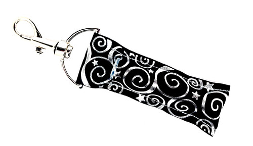 Lip Balm Holder Black with Silver Foil Swirls  Each Lip Balm / Chapstick Holder is HANDMADE with a high-quality material! Our unique design's and clasp offer both style and functionality. The hook is also on a swivel head so the lip balm always falls back down and never gets stuck upside down, this is where most lip balm holders lose your lip balm or chapstick! The holder is designed to snuggly fit any standard chapstick or lip balm. This ensures that the lip balm / chapstick won't fall out when needed most.  BENEFITS: Misplacing or Losing your chapstick is the worst!! Don't let that happen again and buy the perfect solution! Our Lip Balm / Chapstick Holder Keychain will make sure you always have your Gettin Lippy lip balm at hand when desperately needed. Our cute fun designs will compliment anything. Attach it to your keys, lanyard, back-pack, bag, purse, or anywhere your little heart desires with our easy open clasp!  PERFECT GIFTS: A simple gift can go a long way. Everyone needs something cute and functional. Buy now for stocking stuffers, birthday party, a team gift or for a daughter, friend, wife, girlfriend, colleague, student, teacher, etc!   BUY WITH CONFIDENCE: Read the reviews! Our Gettin Lippy Lip balm holders are the number one rated lip balm holders on the market! If you don't LOVE our product, we offer 100% Money Back GUARANTEE no questions asked.  PACKAGE INCLUDES:  1 Unique Lip Balm / Chapstick holder. Each Holder is 6.5 inches (with hook) x 1.5 inches. **NOTE: Gettin Lippy lip balms in pictures are not included but click on the link below and get the best multi-flavored lip balm on the market:   https://gettinlippy.com/gettin-lippyoriginal-line/    HANDMADE IN THE USA!!