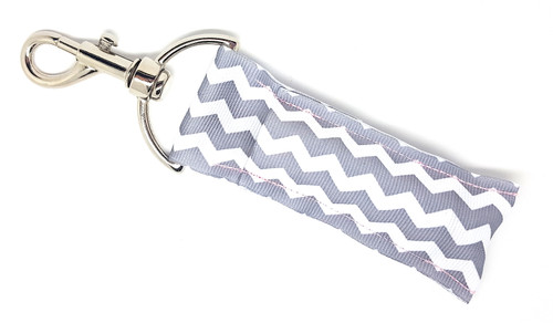 Lip Balm Holder Grey and White Chevron  Each Lip Balm / Chapstick Holder is HANDMADE with a high-quality material! Our unique design's and clasp offer both style and functionality. The hook is also on a swivel head so the lip balm always falls back down and never gets stuck upside down, this is where most lip balm holders lose your lip balm or chapstick! The holder is designed to snuggly fit any standard chapstick or lip balm. This ensures that the lip balm / chapstick won't fall out when needed most.  BENEFITS: Misplacing or Losing your chapstick is the worst!! Don't let that happen again and buy the perfect solution! Our Lip Balm / Chapstick Holder Keychain will make sure you always have your Gettin Lippy lip balm at hand when desperately needed. Our cute fun designs will compliment anything. Attach it to your keys, lanyard, back-pack, bag, purse, or anywhere your little heart desires with our easy open clasp!   PERFECT GIFTS: A simple gift can go a long way. Everyone needs something cute and functional. Buy now for stocking stuffers, birthday party, a team gift or for a daughter, friend, wife, girlfriend, colleague, student, teacher, etc!  BUY WITH CONFIDENCE: Read the reviews! Our Gettin Lippy Lip balm holders are the number one rated lip balm holders on the market! If you don't LOVE our product, we offer 100% Money Back GUARANTEE no questions asked.  PACKAGE INCLUDES:  1 Unique Lip Balm / Chapstick holder. Each Holder is 6.5 inches (with hook) x 1.5 inches. **NOTE: Gettin Lippy lip balms in pictures are not included but click on the link below and get the best multi-flavored lip balm on the market:   https://gettinlippy.com/gettin-lippyoriginal-line/    HANDMADE IN THE USA!!