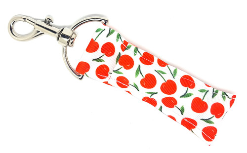Lip Balm Holder White with Red Cherries  Each Lip Balm / Chapstick Holder is HANDMADE with a high-quality material! Our unique design's and clasp offer both style and functionality. The hook is also on a swivel head so the lip balm always falls back down and never gets stuck upside down, this is where most lip balm holders lose your lip balm or chapstick! The holder is designed to snuggly fit nice and cozy any standard chapstick or lip balm. This ensures that the lip balm / chapstick won't fall out when needed most.  BENEFITS: Misplacing or Losing your chapstick is the worst!! Don't let that happen again and buy the perfect solution! Our Lip Balm / Chapstick Holder Keychain will make sure you always have your Gettin Lippy lip balm at hand when desperately needed. Our cute fun designs will compliment anything. Attach it to your keys, lanyard, back-pack, bag, purse, or anywhere your little heart desires with our easy open clasp!  PERFECT GIFTS: A simple gift can go a long way. Everyone needs something cute and functional. Buy now for stocking stuffers, birthday party, a team gift or for a daughter, friend, wife, girlfriend, colleague, student, teacher, etc!   BUY WITH CONFIDENCE: Read the reviews! Our Gettin Lippy Lip balm holders are the number one rated lip balm holders on the market! If you don't LOVE our product, we offer 100% Money Back GUARANTEE no questions asked!   PACKAGE INCLUDES:  1 Unique Lip Balm / Chapstick holder. Each Holder is 6.5 inches (with hook) x 1.5 inches. **NOTE: Gettin Lippy lip balms in pictures are not included but click on the link below and get the best multi-flavored lip balm on the market:   https://gettinlippy.com/gettin-lippyoriginal-line/    MADE IN THE USA!!