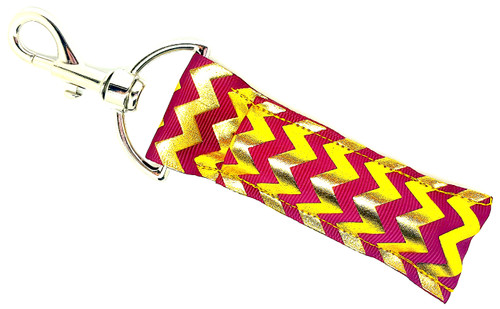Lip balm holder Burgundy and Gold Foil Chevron    Each Lip Balm / Chapstick Holder is HANDMADE with a high-quality material! Our unique design's and clasp offer both style and functionality. The hook is also on a swivel head so the lip balm always falls back down and never gets stuck upside down, this is where most lip balm holders lose your lip balm or chapstick! The holder is designed to snuggly fit nice and cozy any standard chapstick or lip balm. This ensures that the lip balm / chapstick won't fall out when needed most.   BENEFITS: Misplacing or Losing your chapstick is the worst!! Don't let that happen again and buy the perfect solution! Our Lip Balm / Chapstick Holder Keychain will make sure you always have your Gettin Lippy lip balm at hand when desperately needed. Our cute fun designs will compliment anything. Attach it to your keys, lanyard, back-pack, bag, purse, or anywhere your little heart desires with our easy open clasp!   PERFECT GIFTS: A simple gift can go a long way. Everyone needs something cute and functional. Buy now for stocking stuffers, birthday party, a team gift or for a daughter, friend, wife, girlfriend, colleague, student, teacher, etc!     BUY WITH CONFIDENCE: Read the reviews! Our Gettin Lippy Lip balm holders are the number one rated lip balm holders on the market! If you don't LOVE our product, we offer 100% Money Back GUARANTEE no questions asked.   PACKAGE INCLUDES:  1 Unique Lip Balm / Chapstick holder. Each Holder is 6.5 inches (with hook) x 1.5 inches. **NOTE: Gettin Lippy lip balms in pictures are not included but click on the link below and get the best multi-flavored lip balm on the market:   https://gettinlippy.com/gettin-lippyoriginal-line/     MADE IN THE USA!!