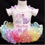 image of a 2nd birthday outfit girl featuring a little light purple dinosaur with a little pink bow and a pastel rainbow glitter 2. This baby dress with tutu has a fluffy ribbon trimmed tutu also with pastel rainbow colors.