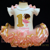 image is of a 1st birthday outfit for girl,  it features a little ballerina and a gold glitter number 1. This baby tutu dress is made with light pink satin and gold metallic ribbon