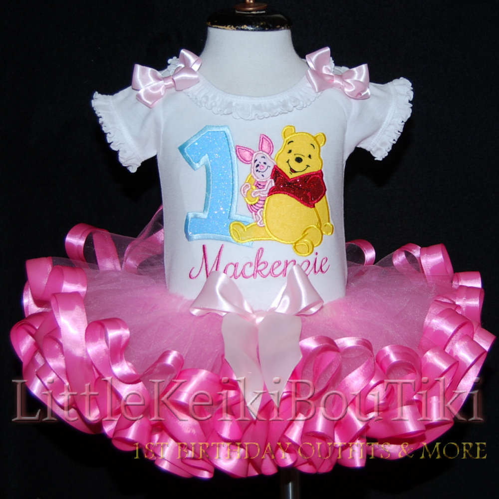 image of a birthday 2 piece outfit  featuring Winnie The Pooh, this baby dress with tutu is made with a  ribbon trimmed tutu in bright pink.  A beautifully embroidered design of  Winnie the Pooh and Piglet finishes off this high quality baby dress with tutu