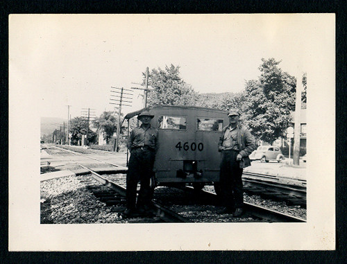 Snapshot of Two Railroad Workers Standing on Train Tracks