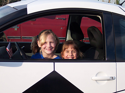 Two young soccer players in the Code Four Athletics Soccer Uniform Shop Soccer Ball Car.