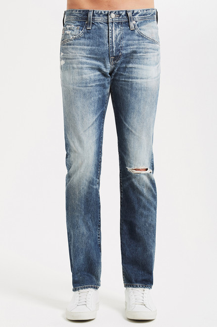 "The Tellis by AG Modern Slim Jean for men features an authentic, 20-year vintage midblue denim wash that's been uniquely distressed to mimic a pair of genuine vintage jean.  The Tellis is cut with a fitted upper block and tapered leg opening. This men's pant is designed in a midweight denim fabric spun with 100% cotton.      Fits true to size.     Front Rise: 9.75"" Knee Opening: 16"" Bottom Opening: 14"" Inseam: 33"""