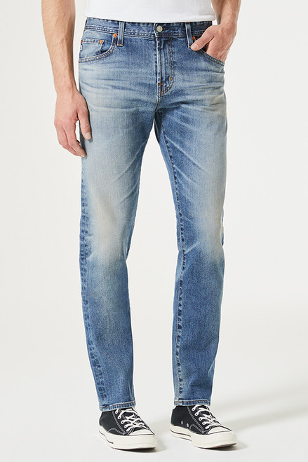 "The Graduate By AG Tailored Leg Jean for men features a lived in blue denim wash with placement fading and 3D whiskering, a slim mid rise waist, and  a relaxed fit at the hip to the knee before tapering at the leg opening. This men's slim straight jean is designed in a midweight denim blend with added stretch for a classic, structured feel with comfortable wear.       Fits true to size.     Front Rise: 9.75"" Knee Opening: 17"" Bottom Opening: 15.5"" Inseam: 34"""