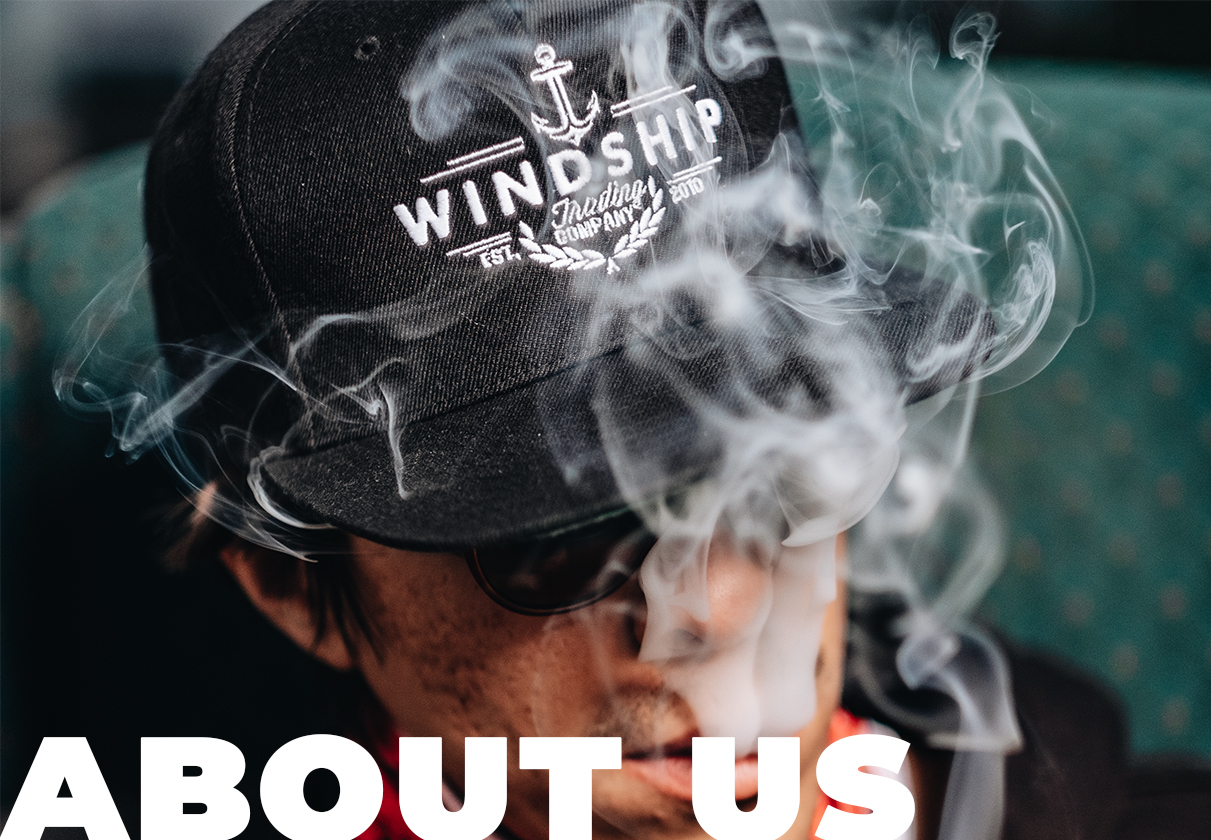 Guy exhaling smoking with hat and shades on