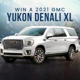 White 2021 GMC Yukon Denali XL with mountains and snow