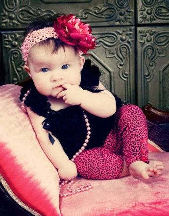 Little baby girl with blue eyes, pink pearl, pants and a flower in her hair sitting on a pink sofa with a green backdround.