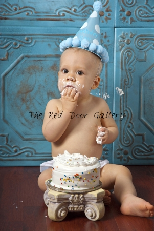 A Portrait of a boy eating a cake, sitting on a brown floor and wearing a blue birthday hat with white dots.