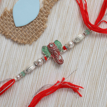Gifting Ganesha is a sign of prosperity. This designer Ganesha Rakhi is made in German silver metal with engraved  beads and traditional premium quality red thread.