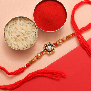 Flower shaped metal Rakhi with beautiful glittering crystal in-between, wove in traditional red thread with beads.