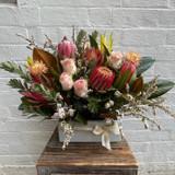 Arrangement of roses and wildflowers in ceramic pot