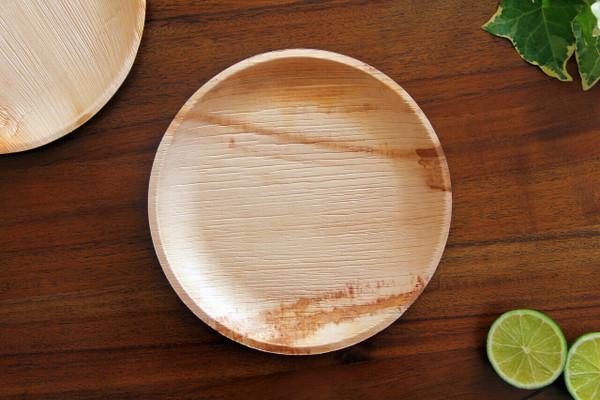 FOOGO Green 8 inch round medium areca palm plates in a dark woody background