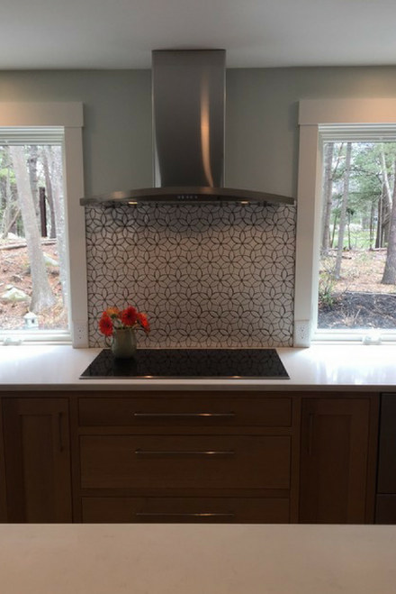 White handmade tile backsplash with dark gray grout and stainless steel hood
