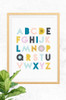 Alphabet print with grey background, frame in oak and mounted on a concrete wall. The letters of the alphabet are pastels, bright blues and mustard golds, all on a light grey background.