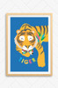 A sleeping tiger, illustrated in bright oranges and wearing a colourful bowtie. Set on a bright blue background with the word tiger playfully written underneath. Framed in an oak from and mounted on a wall.