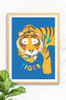 Our latest big cat print featuring a sleepy tiger on a bright blue background. Digitally illustrated with the word tiger underneath his body in colourful type.