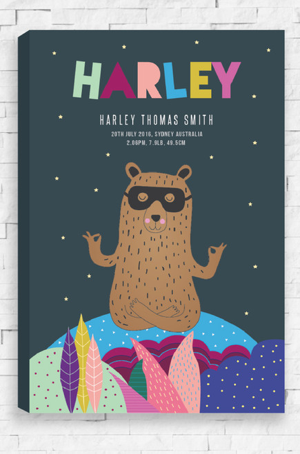 A ready to hang canvas with a personalised birth details of a child written at the top in a fun font. Sitting below on a charcoal colored background, a brown masked bear sits meditating on top of a colorful landscape.