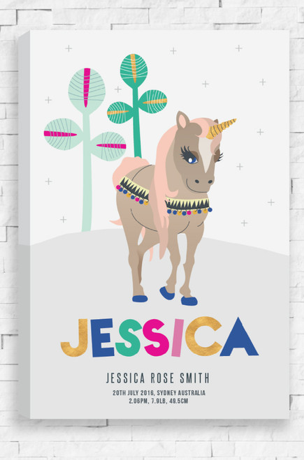 A ready to hang canvas that features personalised details of a child at the bottom. Their first name in a larger font that is arranged in a fun way, and below the finer details in a san serif font. Above is a beige unicorn, with a gold horn and coral colored hair. It's bridal is decorated with colored beds and it's hooves are blue. The unicorn walks along a grey hill with two minimal aqua plants behind.