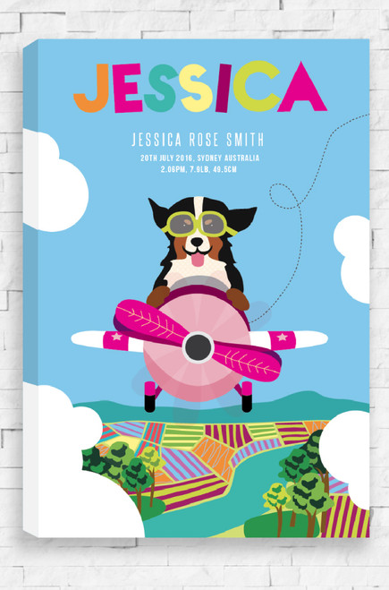 At the top of the canvas is the personalised name of a child designed in a uneven, playful font. Each letter is a different colour and underneath in a white sans serif font are the finer birth details. At the front and centre of this design is an illustration of a dog, zooming through the blue sky flying a magenta colored plane. Below are crops and a river and white, puffy clouds either side of the canvas.