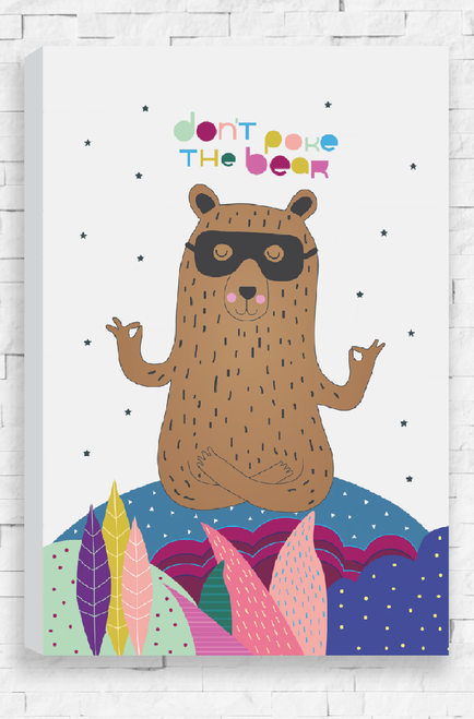 A canvas with an illustration of a colorful, detailed landscape with a meditating, brown bear sitting atop. With it's legs crossed and arms out, the bear has a peaceful smile and its eyes closed. It wears a black Zoro-like mask and is placed on a light grey background scattered with charcoal stars. Above the bear's head are the words 'Don't Poke The Bear'.