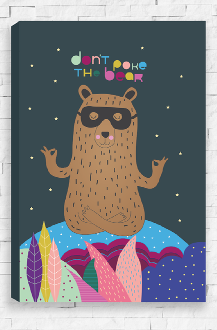 An illustration of brown bear with a thin black outline and fine hair detail. It is wearing a black eye mask and has it's eyes closed and body in a meditation stance. With crossed legs, the bear sits on a blue hill with colorful plants, dotted with pattern detail below. In the background is a dark charcoal night sky with stars and the words 'Don't Poke The Bear' written above it's head. A stretched, ready to hang canvas.