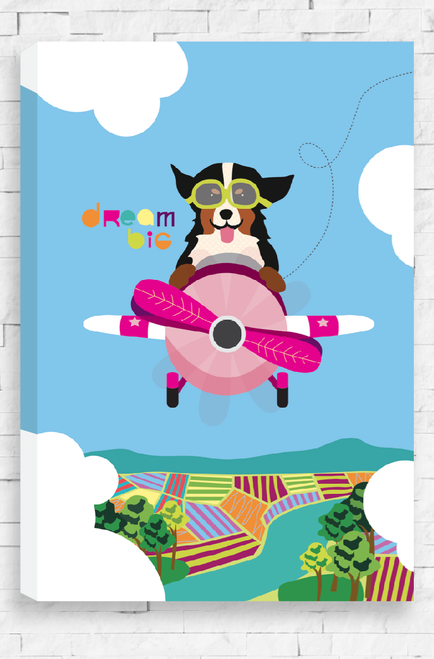 An illustrated canvas hanging on a wall. It features a happy dog with it's tongue hanging out and ears flapping. It is flying a bright pink old style airplane  through a blue sky with farms and a river below. Dotted lines behind the plane indicate that it has been on a wild ride. Next to the dog are the words Dream Big.