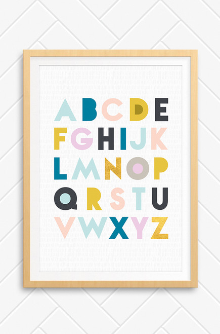 This image shows Luca Rose Designs Alphabet print with an oak frame sitting on a concrete wall with a green plant in the bottom left corner. The wall art print features all the letters of the alphabet in a rows, each in a differing pastel colour, contrasting with charcoal grey and mustard colours. The background is a light grey with a subtle pattern of hand drawn strokes in lines running across it.