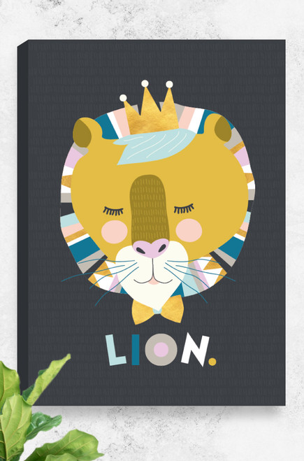 Lenni Lion, a ready to hang canvas, hung on a concrete wall with a plant in the bottom corner. The artwork features an illustrated lion wearing a crown and a bowtie. The face uses mustard colours and is contrasted with pastel hues. The word LION is arranged in a playful manner underneath the face. The background a dark charcoal with a hand drawn line pattern.