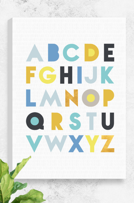 Luca Rose Designs 'Alphabet' canvas which features all the letters of the alphabet in a modern typeface across 5 lines. The letters are coloured with calming blues, golds and yellows, all sitting on a fresh light grey patterned background. The canvas is 100% Australian made and designed and comes stretched and ready to hang.