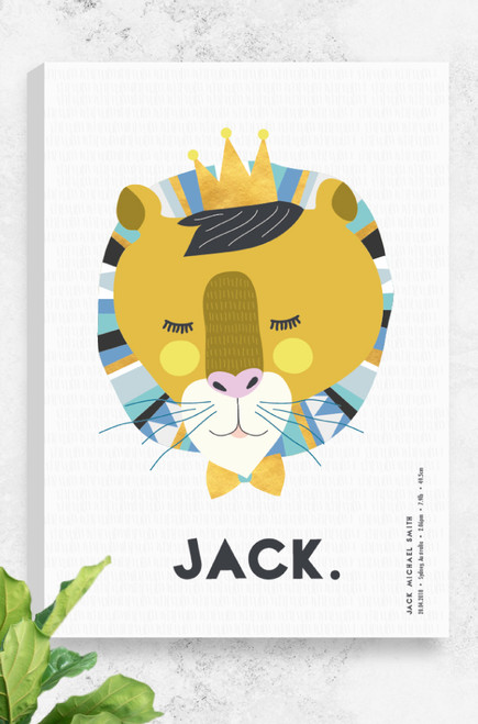 A stretched, ready to hang canvas designed by Luca Rose Designs. The artwork features a sleeping lion created with mustard and brown hues on the face, surrounded by a patterned mane in calm blue tones. The peaceful lion wears a golden crown and matching bow tie. Underneath the drawing is room for the name and birth details of a boy or girl. The first name is written in a large modern font in the centre. In the right hand corner are the other details, running vertically in a smaller font. The background is a light grey.