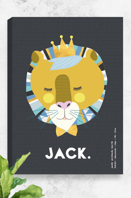 A quirky wall art canvas by Luca Rose Designs with personalised name and birth details at the bottom. A brightly coloured lion wearing a crown and bowtie pop from a dark charcoal background. It's mane features an aztec style pattern in bright blues and gold. The custom order child's name is written in stunning white in the bottom centre of the canvas, arranged in a playful sans serif font, with the birth details running vertically from the bottom right corner. The artwork is shown hanging on a concrete wall with a fiddle leaf fig in the corner.