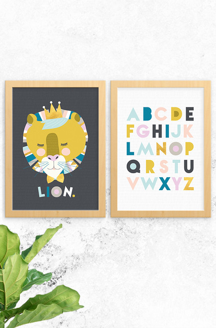 Luca Rose Designs 2 pack wall art prints Lenni Lion in charcoal background and Alphabet poster with light grey background. Both are framed with an oak frame and mounted on a concrete wall.