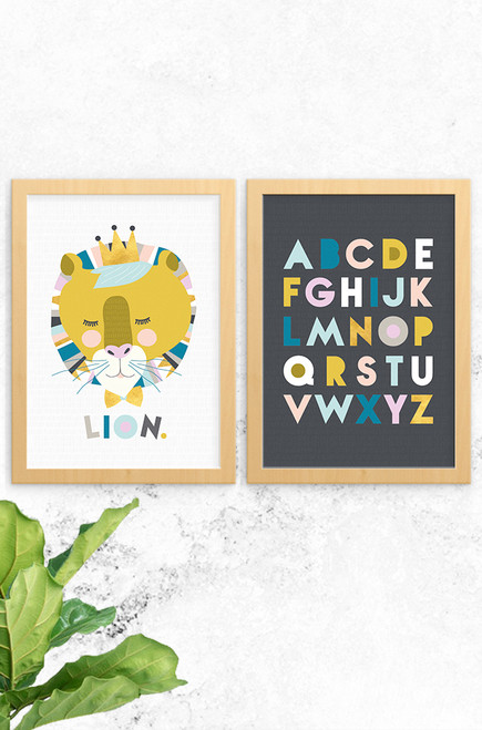 2 pack of prints Lenni Lion and Alphabet artwork designed by Luca Rose Designs. With a grey and charcoal background, both use a calming yet bold colour palette. Mounted in oak frames on a concrete wall.