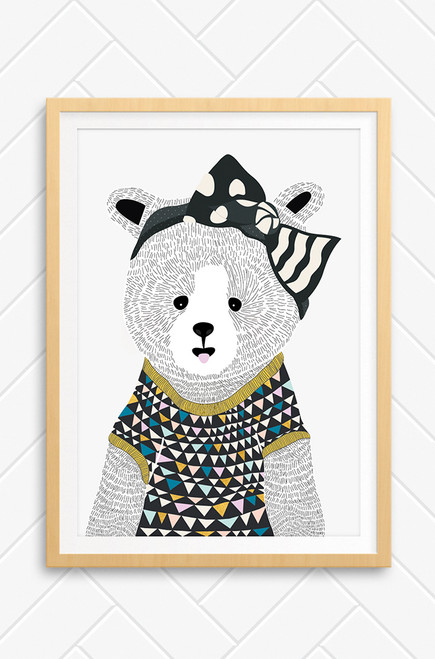 An illustrated bear called 'Eva' by Luca Rose Designs. The print features a hand drawn bear, wearing a large black bow and patterned t-shirt with a gold trim. The artwork is coloured with black, golds, and pale pastel tones, all set on a light grey background. The print is framed in an oak frame and set on a concrete wall.