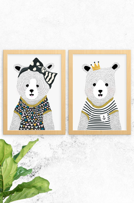 A photo of 2 wall art prints designed by Luca Rose Designs. Both artworks feature a hand drawn bear, a girl on the left, Eva, and Noah, a boy on the right. They have been designed using intricate hand drawing, Eva wearing a large black bow on her head and Noah, a nautical themed outfit. Both are framed in an oak style frame.