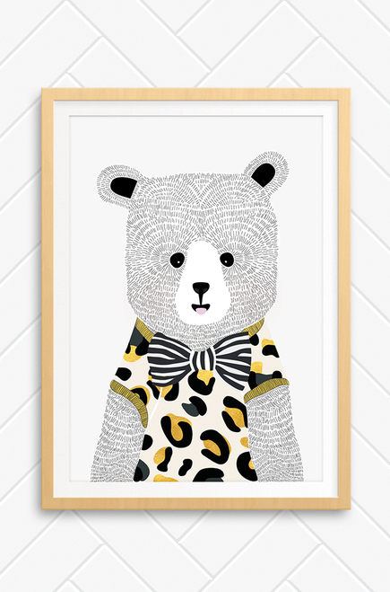 A framed version of Luca Rose Designs 'Ted Bear' wall art print for kids bedroom. The illustration features a cute bear that wears a leopard print t-shirt with gold trims and a bold, black and white striped bow tie. His hair is hand drawn and he has friendly looking features.