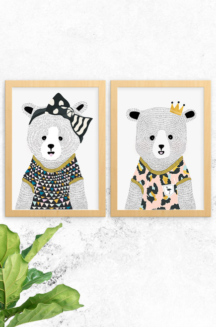 An image of 2 wall art prints designed by Luca Rose Designs. Both prints feature a female bear, one named Eva and the other Emma. Eva wears a giant black bow and triangle pattern t-shirt. Emma, dressed in a pale pink leopard print shirt with a golden crown. Both have been hand illustrated with detailed fur.
