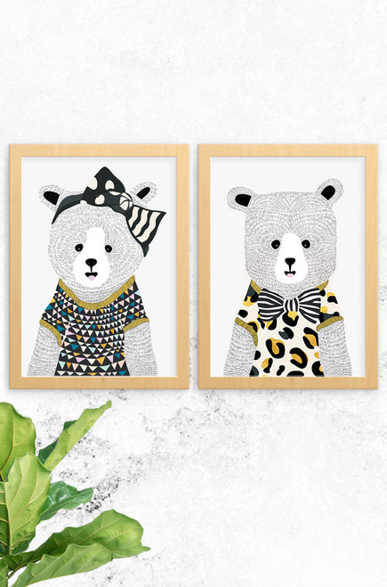 An image showing our 2 pack of Bear prints. On the left Eva Bear wears an oversized black bow and bold patterned t-shirt. Noah Bear, sitting next to wears a leopard print t-shirt with a black and white striped bow.  Both bears have been hand illustrated with detailed fur and facial features, and framed in an oak finish timber.