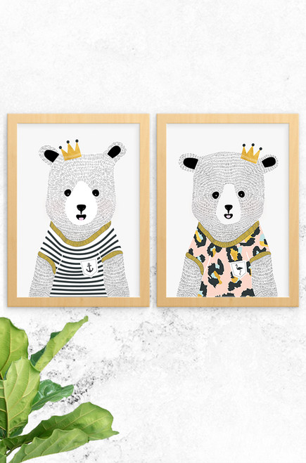 The photo features the Noah and Emma Bear wall art prints by Luca Rose Designs. The bears have been hand illustrated and both wear funky t-shirts with gold trims. Noah is dressed in black and white stripes and Emma in pale pink leopard print, both with a sweet golden crown on their heads.