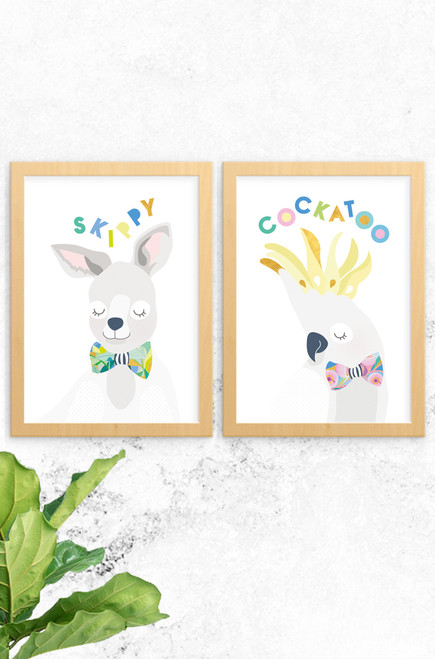 A 2-pack of prints featuring a  kangaroo named skippy and an energetic cockatoo. Both are digitally illustrated in pastel colours, with a bright and patterned floral bowtie. Each have the name of the animal written at the top in a fun typeface arranged playfully. Also available a koala and budgie, why not complete the wildlife collection!