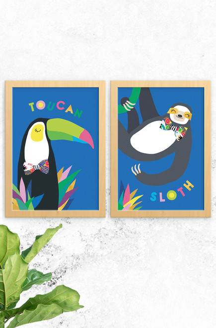 A 2-pack of illustrated kids wall art prints one featuring a toucan and the other a sloth. Vibrant colours contrasting with greys and blacks of the animals.  Both artworks have typography playfully arranged at the top and bottom.