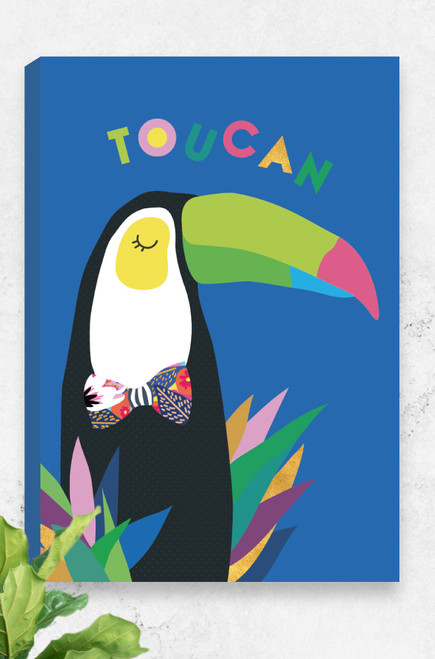 A colourful ready to hang canvas featuring a bold and happy toucan. It wears a patterned bowtie and is perched with bright leaves around his body. The word toucan is playfully arranged above his head. Placed on a bright blue background, this artwork is a standout for any jungle themed room.