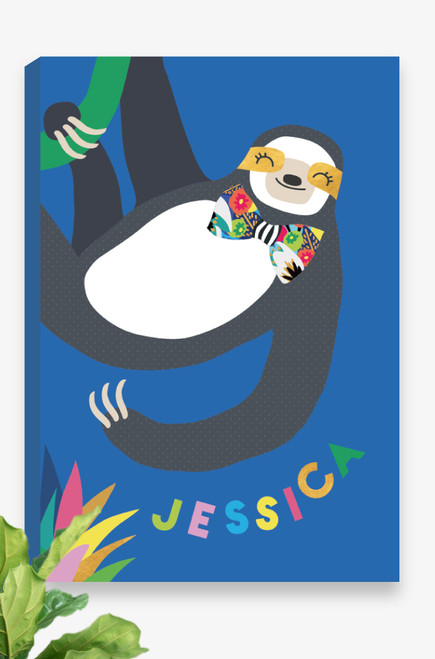 A ready to hang canvas with a happy go lucky sloth hanging from a green vine from the top of the artwork. He has gold patches behind his friendly eyes and a vibrant bow-tie around his neck. Personalised underneath in a playful font with the name of a child. A perfect gift idea for a new baby girl.